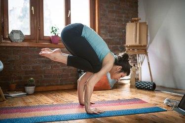 Woman doing crow yoga pose for balance
