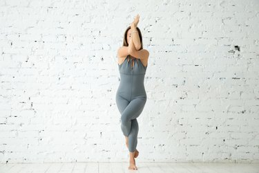 Woman doing Eagle standing yoga pose for balance