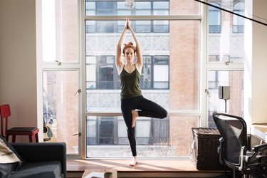 Woman doing Tree standing yoga pose for balance