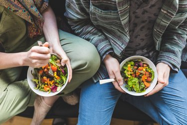 Couple eating healthy salad at home on the sofa