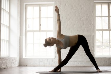 Woman doing Triangle standing yoga pose for balance