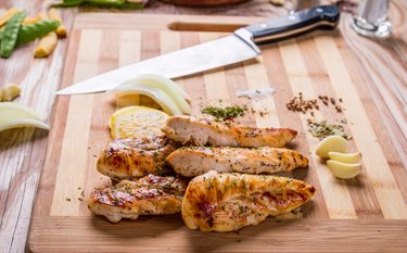 Grilled chicken breasts on a cutting board after grilling on a gas grill