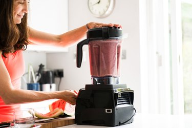 Woman making smoothie with collagen supplements in kitchen