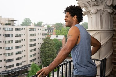 Errick stands on his balcony