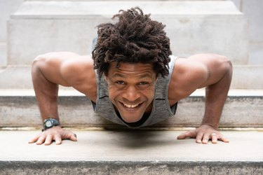 Errick smiles while doing a push-up