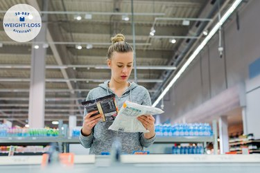 A woman reading nutrition labels on frozen food items in a supermarket