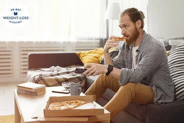 man sitting on couch eating pizza and holding TV remote