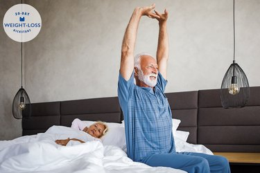 man in pajamas stretching before he gets out of bed next to sleeping spouse