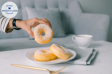 a woman's hand reaching for a doughnut on a coffee table with mug and fork