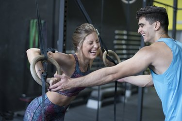Man helps laughing woman with ring training with complicity