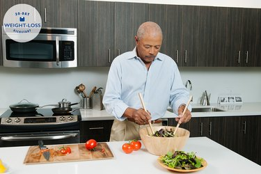 An older man making a salad in his kitchen