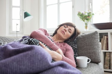 Woman lying on couch and feeling uncomfortable after eating