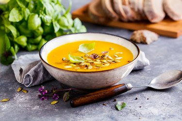 Pumpkin soup in a bowl with pepitas on top