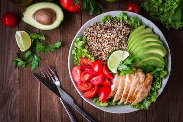 Healthy salad bowl with quinoa, tomatoes, chicken, avocado, lime and mixed greens (lettuce, parsley) on wooden background top view. Food and health