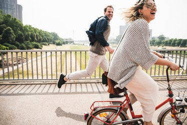 Woman riding bike, man running after her laughing