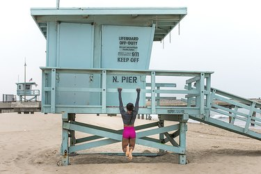 woman doing Shoulder Hanging exercise on lifeguard tower on the beach