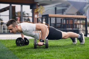 Man doing a push-up renegade row with dumbbells during dumbbell challenge back and shoulder workout