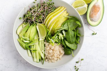 Gluten free quinoa veggie bowl with spinach, sprouts, pear, lime, cucumber and quinoa
