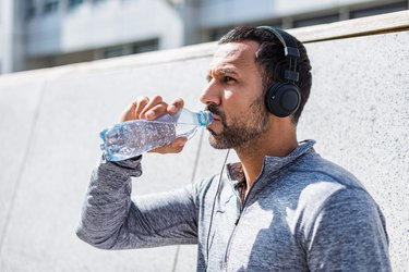 Man working out in headphones drinking water