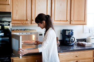 Woman adding frozen meat to microwave