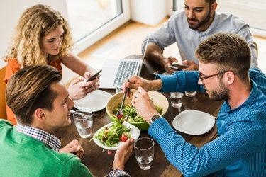Women and men having a working lunch, man serving salad
