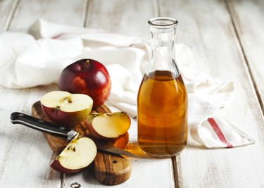 Apple cider vinegar with apples on a table