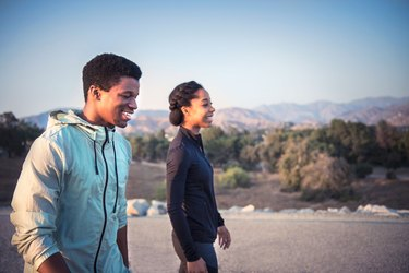 Woman and man walking a mile a day for weight loss exercise