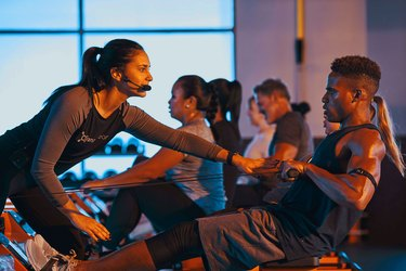 Group of people doing an Orangetheory Fitness workout on rowing machines
