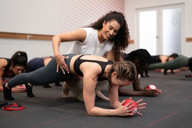 Trainer helping women during a Pure Barre workout class