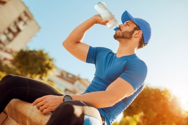 Thirsty athlete man drinking water