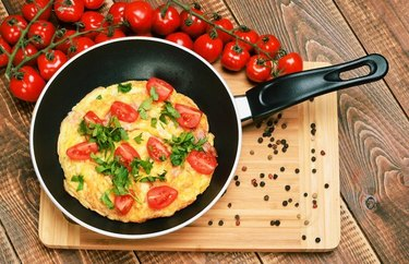 Breakfast-for-Dinner in a skillet on a wood serving board with vined tomatoes