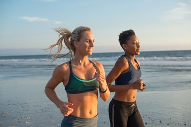 Two runners running on the beach during sunrise or sunset on vacation travel fitness workout