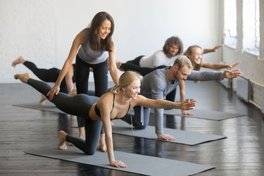 Woman assisting woman in a group workout class