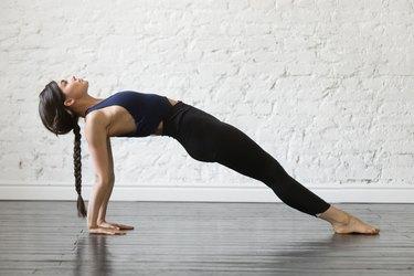 Woman holding upward plank pose on studio background