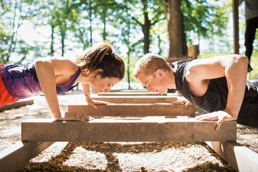 Man and woman doing push-ups outside in park on a nice day