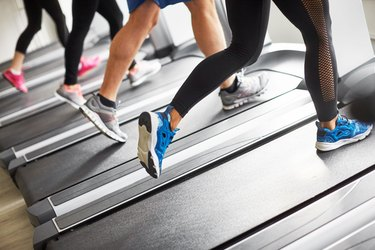 Group of people jogging on treadmills at the gym, legs and sneakers shown
