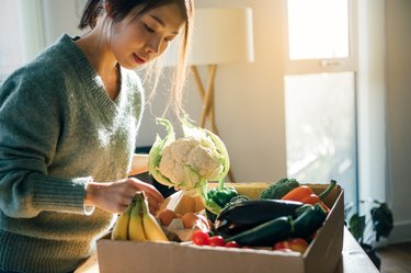 woman unpacking cardboard box of groceries holding cabbage