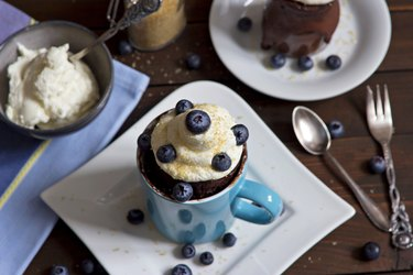 High-protein mug cake with blueberries on white plate on table