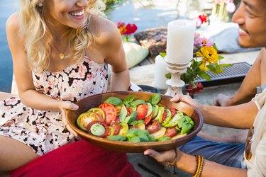Man and woman passing a tomato salad at a summer picnic