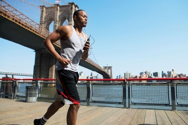 Man running in New York City near Brooklyn Bridge using a half-marathon training schedule for beginners.