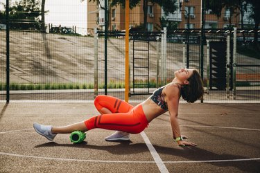 Woman foam rolling her calf muscle for post-marathon recovery