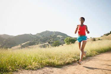 Woman running on a hilly trail to train for an ultramarathon