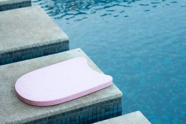 Pink kickboard by the side of a pool to help teach swimming lessons to become a better swimmer