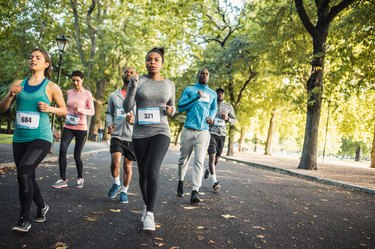 Runners in a park competing in a race following a marathon training schedule for beginners