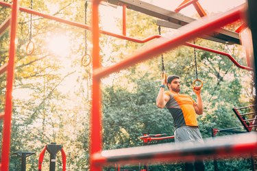 Man using rings for a playground workout.