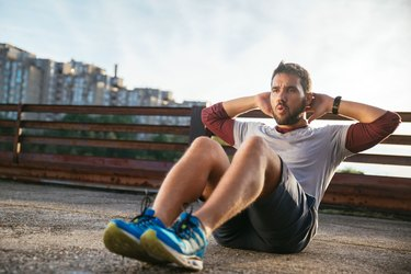 Man performing sit up exercise to reduce stomach size