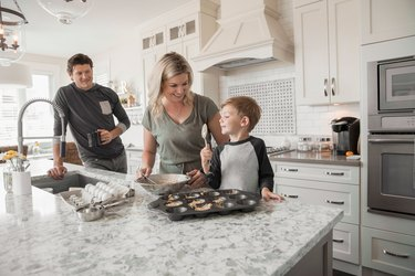 Family baking muffins in kitchen