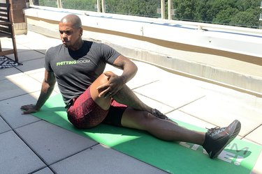 Fhitting Room trainer demonstrating how to do seated spinal twist