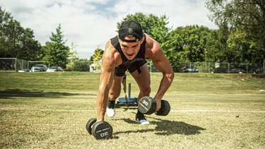 man lifting weights while sprinting down a field