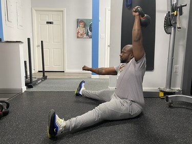 Man doing a seated overhead press with a kettlebell during an arm workout